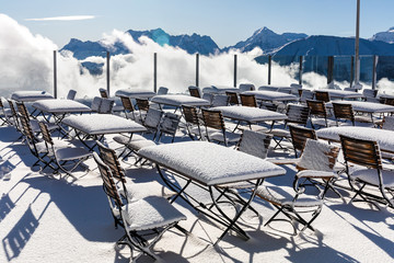 Outdoor restaurant terrace covered in snow in the winter in the mountains. Alps, Switzerland