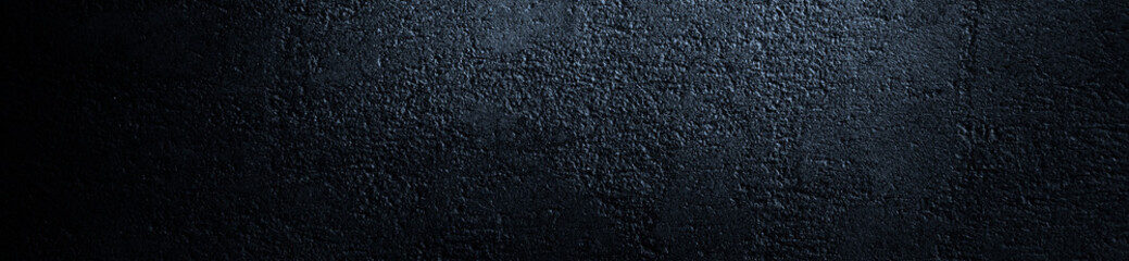 Black grunge background. Bright web banner. Reflection of light on a rough concrete wall. Copy space for your design. Wall mural