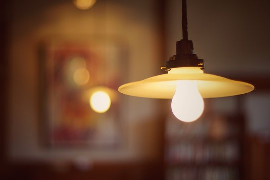 Close-Up Of Illuminated Light Bulb Hanging In Room