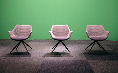 Three empty chairs in a TV studio with green screen background