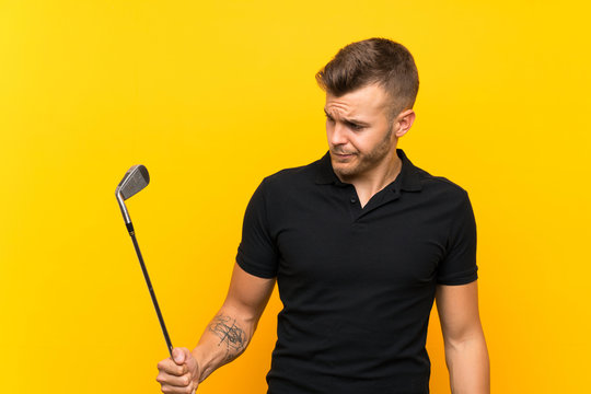 Golfer player man over isolated yellow background with sad expression