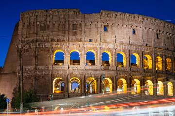 Wall Mural - Rome, Italy - Jan 2, 2020: Colosseum at night with colorful blurred traffic lights