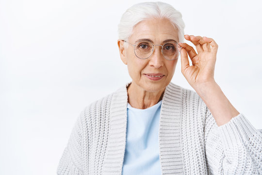 Health, insurance and retirement concept. Cheerful elegant old lady in cozy outfit, grey combed hair, fixing presctiption glasses, picking new eyewear for better sight at opticians, smiling pleased
