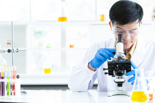 Senior Scientist looking through microscope in modern laboratory. Confident male health care professional in his working environment or researching about chemical in laboratory.
