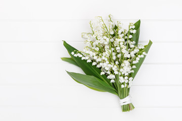 Wall Murals Lily of the valley Lilly of the valley flowers and leaves bouquet on light background.