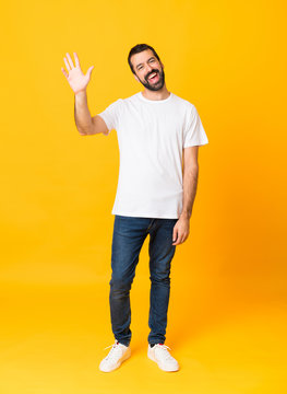 Full-length shot of man with beard over isolated yellow background saluting with hand with happy expression