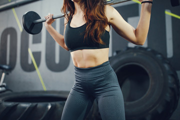 Beautiful girl in the gym. Girl with a sports body.Woman with a barbell