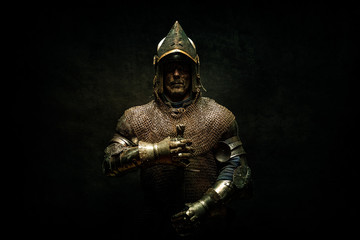 Portrait of a knight in armor holding his sword in his hands