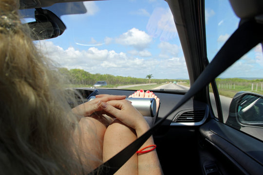 Full Length Of Woman Sitting With Feet Up On Dashboard In Moving Car