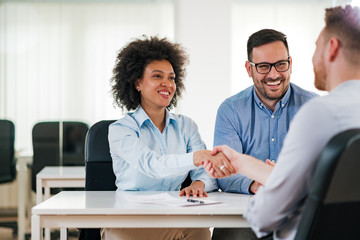 Smiling HR managers handshake with a job candidate.
