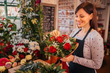Obraz Happy florist holding beautifully decorated bouquet, portrait. - fototapety do salonu