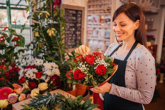 Happy florist holding beautifully decorated bouquet, portrait.