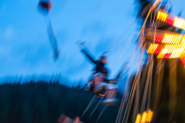 Fotomurales - Blurred Motion Of Illuminated Chain Swing Ride At Dusk