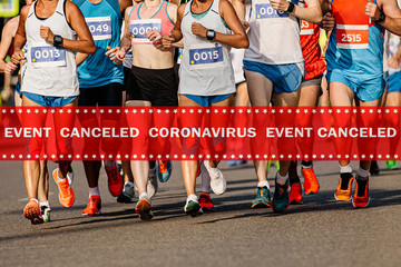 Fototapete - warning tape event canceled coronavirus in background group of runners running marathon