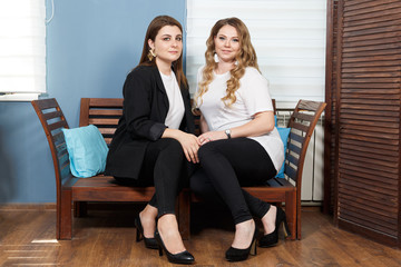 Two Young Women Models Plus Size. Close-up Portrait. Sitting in a room