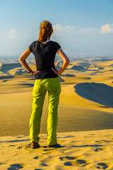 Girls watching desert sand dunes in sunset light, Huacachina oase, Ica, Peru, South America