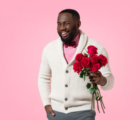 Handsome man holds bouquet of roses. Photo of african american man expresses love to someone, romantic feelings on pink background. Be my Valentine