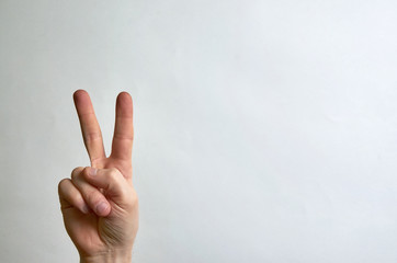 Two fingers up on the hand, peace symbol on a white background with a sweep for text