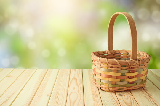 Empty basket on wooden table over green bokeh background. Spring and easter mock up for design.