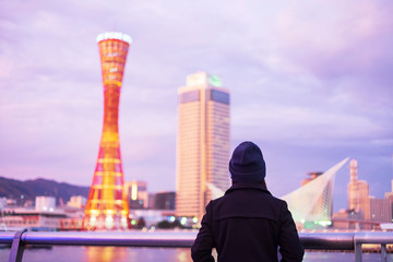 Fototapete - Young woman traveling at Kobe port near Osaka, Happy Asian traveler looking beautiful modern buildings at sunset. landmark and popular for tourist attractions in Kobe, Hyogo, Japan.Asia Travel concept