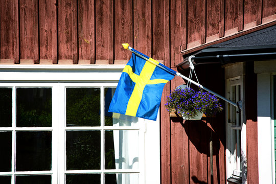 Swedish flag at the entrance of a typical swedish wooden house