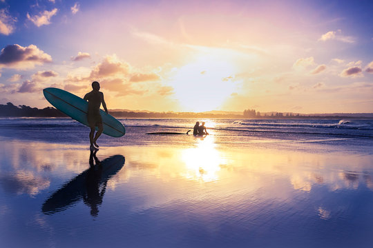 Full Length Of Man Walking With Surfboard By Silhouette People Sitting At Beach