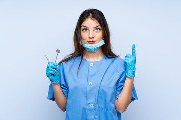 Woman dentist holding tools over isolated blue background pointing with the index finger a great idea