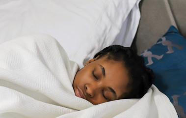 African-American teenaged girl sleeping in a bed