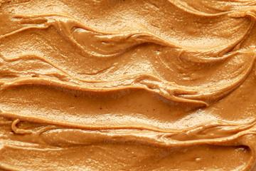Fresh smooth Peanut Butter closeup background, texture