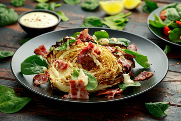 Oven roasted cabbage steaks with bacon, spinach and mayonnaise. healthy food