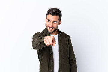 Young handsome man with beard over isolated white background points finger at you with a confident...