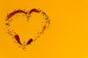 Heart mosaic of spices pepper, garlic, coriander on orange background with copy space