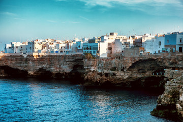 View of rocky seashore with town buildings. Polignano a Mare, Italy. Fotomurales
