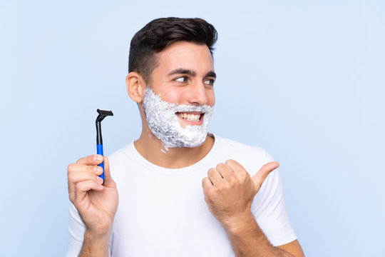 Young handsome man shaving his beard over isolated background pointing to the side to present a product