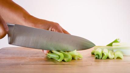 hand cutting celery on board