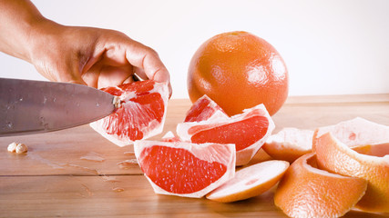 hand seeding grapefruit with the tip of knife