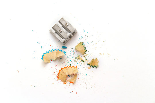 Metal pencil sharpener and colored sawdust from pencils on a white background