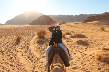 A woman rides a camel near dried bushes through the Wadi Rum desert in Jordan and simultaneously tries to take pictures. Sandstone mountains in the background.
