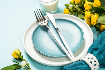 Spring table setting with flower on blue.