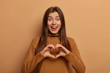 Portrait of lovely joyful woman shapes heart gesture over chest, expresses love and sympathy to boyfriend, has funny expression, long dark hair, dressed in brown turtleneck. Be my valentine. Wall mural