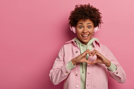 My heart is for you. Glad teenage girl makes heart gesture over cest, expresses affection, giggles positively, listens audio track in headphones, stands over pink wall. Body language concept