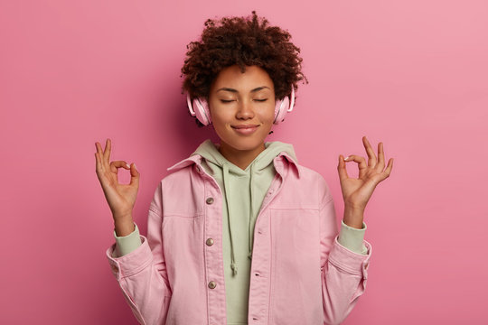 Relaxed beautiful woman makes zen gesture, meditates while listens peaceful music in headphones, has relaxation session during spare time, closes eyes, wears stereo headphones and sweatshirt