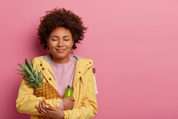 Pleased curly Afro American woman has healthy nutrition, holds ripe pineapple and green smoothie, closes eyes with satisfaction, wears yellow anorak, keeps fresh fruit in hands, models indoor
