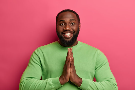 Photo of handsome relaxed man holds palms in pray, finishes yoga session, smiles positively, wears green sweater, isolated over pink background, looks with gratitude, thanks friend for help.
