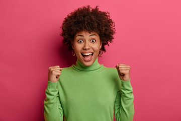 Excited overjoyed curly ethnic female celebrates as wins prize, screams loudly, makes fist pump, feels lucky and pleased, becomes champion, wears casual jumper, happy about recent amazing news