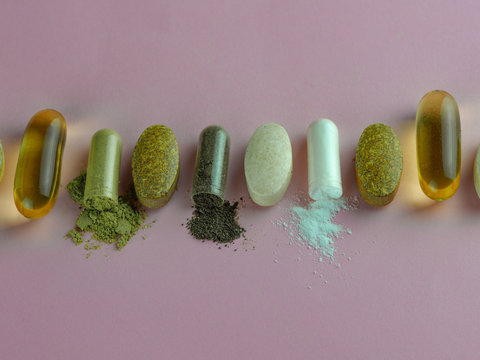 opened capsule biologically active drugs pills food supplements healthy at PINK background
