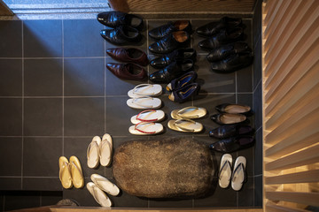 Leather shoes and traditional Japanese sandals arranged in entryway