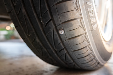 Close-up nail or screw stick on the car tire, the most problem of flat tire