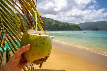 Coconut drink on sand beach, summer vacation on beach on the remote island in the middle of the ocean.