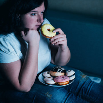 Overweight depressed woman laying on sofa eating sugary food watching TV. Sugar addiction, unhealthy lifestyle, weight gain, dietary, healthcare and medical concept.
